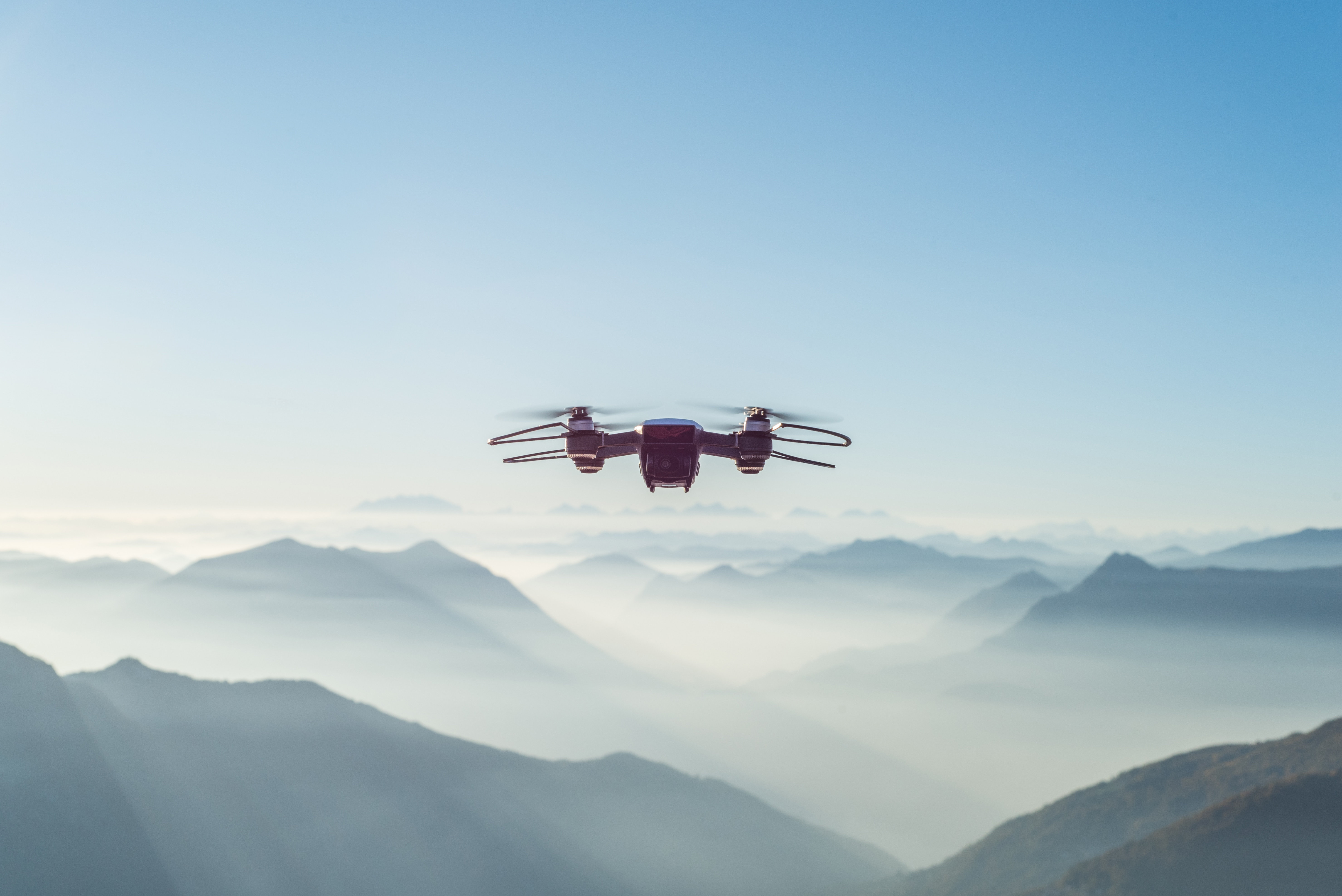 four propeller drone flying above the clouds in a mountain scape