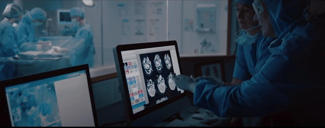 醫生看著螢幕上的超音波,而外科醫生在背景進行手術