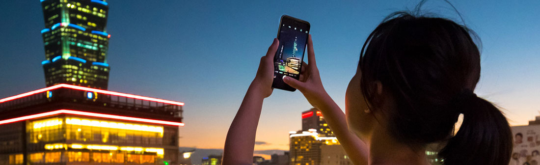 Woman taking picture of building at dusk with her phone