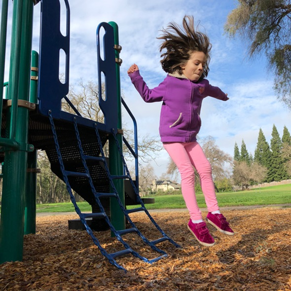 Young girl jumping off of a playground at a park
