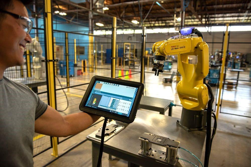 Man looking at tablet while programming a robotic arm on an assembly line