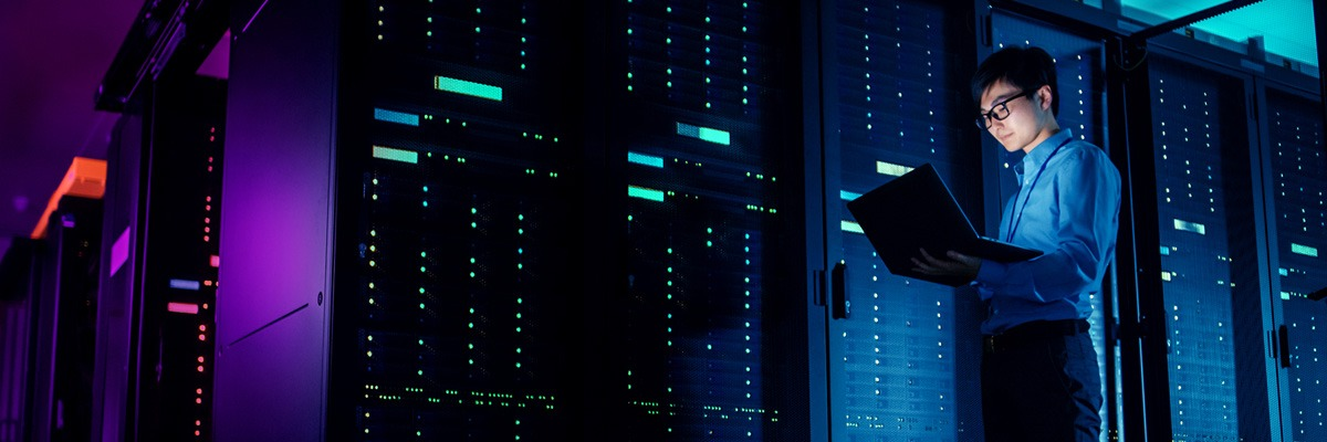 Man standing in dark data center looking at his laptop with LED lights light up on servers