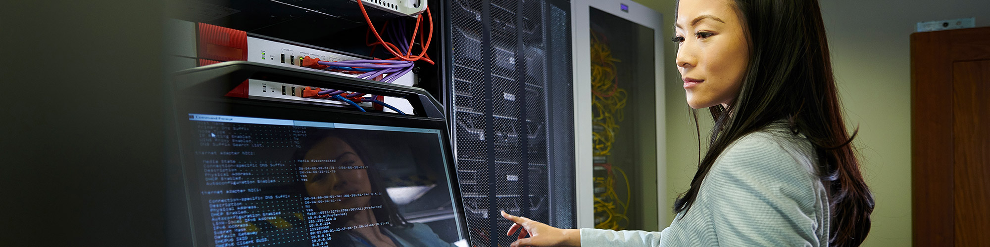 Woman looking at HTML code on a screen in a data center