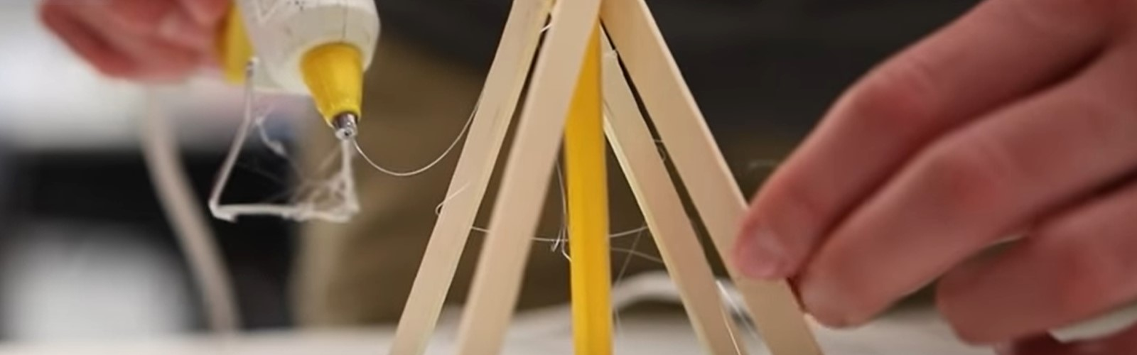 Popsicle sticks and a glue gun being used to build a teepee
