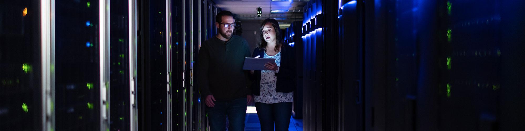 Woman showing man tablet near servers