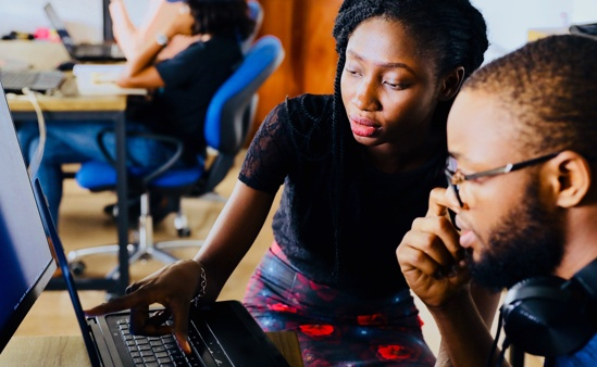 Man and Woman of Color collaborating over a resume on a laptop