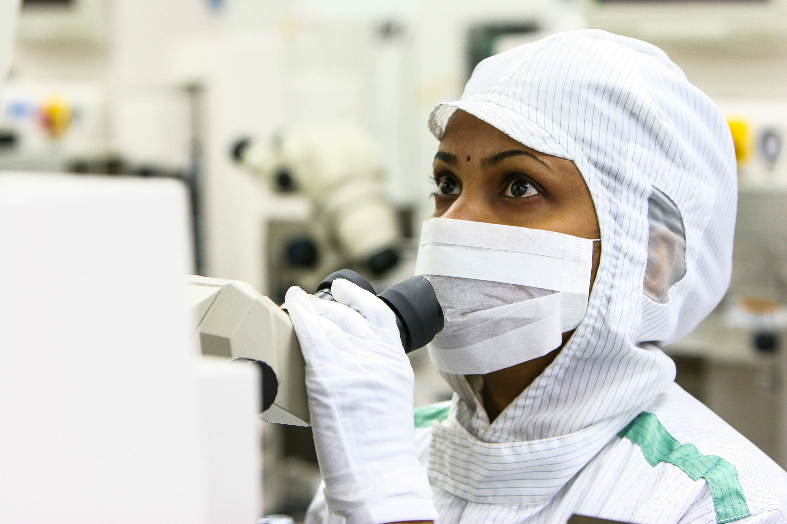 Image of female scientist looking at microscope