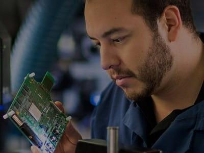 Man in lab coat inspecting FPGA board