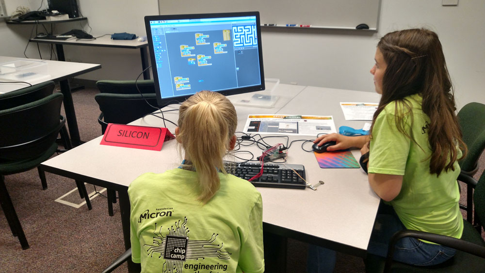 Two girls at Micron Chip Camp working on a computer
