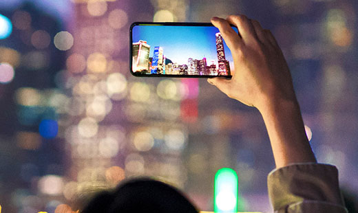 A person holding their phone above their head  taking a picture of a city skyline at night