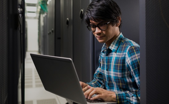 在伺服器房使用筆記型電腦工作的有色人種男性
