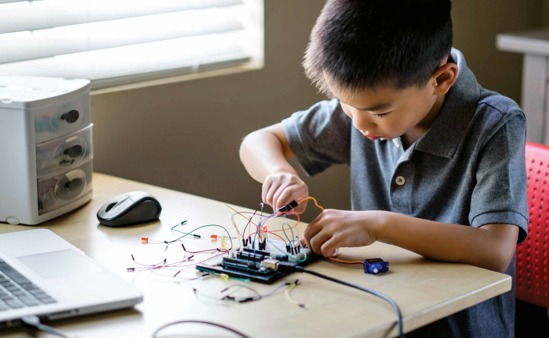 Young boy learns the fundamentals of programming with a simplified motherboard